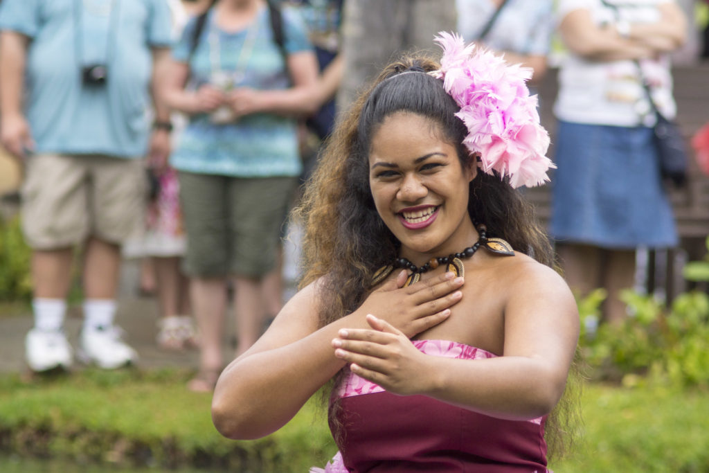One of the dancers of the Polynesian Cultural Center dancing on a boat in the river for tourists to view.